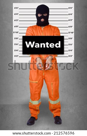 Prisoner with handcuffs standing wearing a balaclava camouflage face in jail against gray police lineup or mug shot word wanted - stock photo