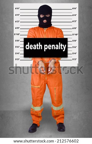 Prisoner with handcuffs standing wearing a balaclava camouflage face in jail against gray police lineup or mug shot word death penalty - stock photo