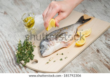 Process of cooking Dorado fish with lemon, olive oil and herbs - stock photo