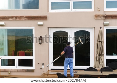 Professional window washer cleaning house windows with de-ionized water using an extension pole - stock photo