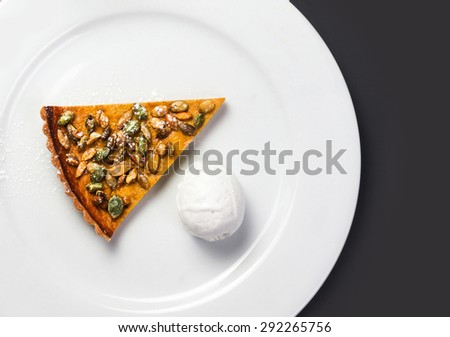 Pumpkin Pie with whipped cream and pumpkin seeds on white plate over black chalk board. Beautiful autumn Pumpkin thanksgiving pie  - stock photo