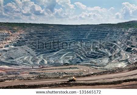 quarry extracting iron ore with heavy trucks, excavators, diggers and locomotives