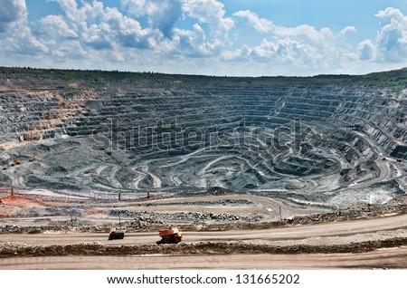 quarry extracting iron ore with heavy trucks, excavators, diggers and locomotives - stock photo