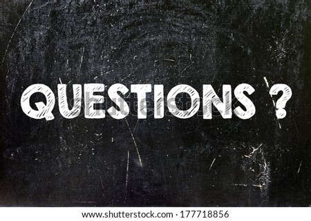 Questions handwritten with white chalk on a blackboard - stock photo