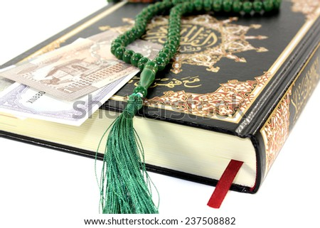 Quran with Pakistani rupee before light background