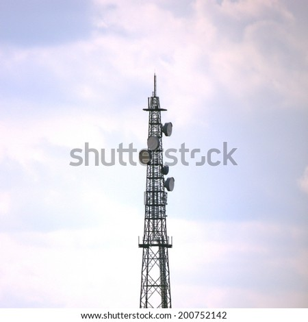 Radio tower and clouded sky, bearing dishes.
