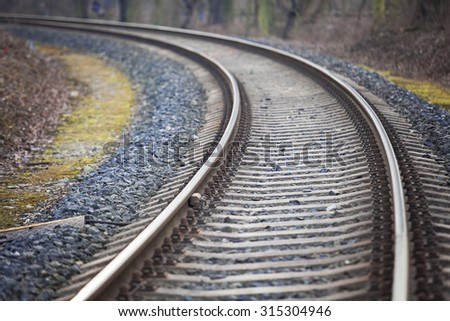 Railway track leading into the unknown through a forest - stock photo