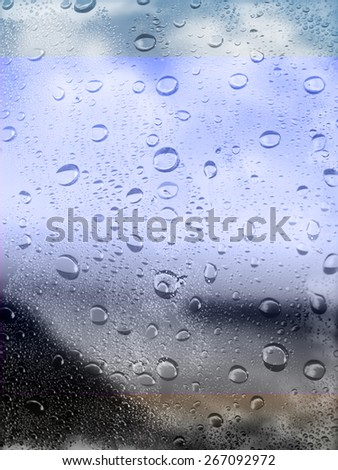Raindrops on the window glass and color of light          - stock photo
