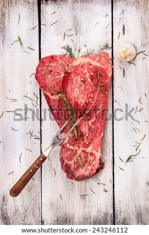 raw beef  with meat fork on old white gray wooden background, top view - stock photo