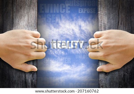 """REALITY"" text in the sky behind 2 hands opening the wooden door. - stock photo"