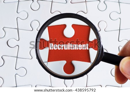 """Recruitment"" text on red missing jigsaw puzzle with man right hand hold black magnifying glass searching for missing puzzle peace - business and finance concept - stock photo"