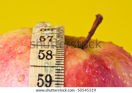 Red apple and measuring tape, isolated on yellow - stock photo