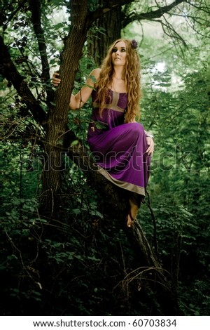 red-haired girl in wood on the tree - stock photo