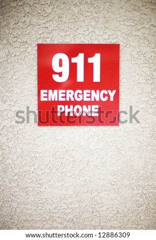 911 red square sign on stucco wall