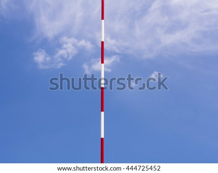 red white antenna net for beach volleyball and a blue sky with clouds in the background  - stock photo
