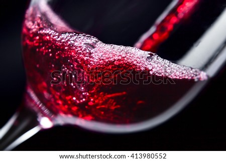 Red wine in wineglass on dark background - stock photo