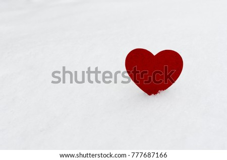 red  wooden heart in snow