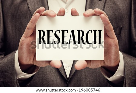 """""""Research"""" written on a signboard in businessman's hands - stock photo"""