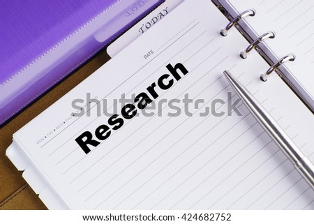 """Reseearch"" text on notebook on a wooden table with open diary and pen - conceptual images"