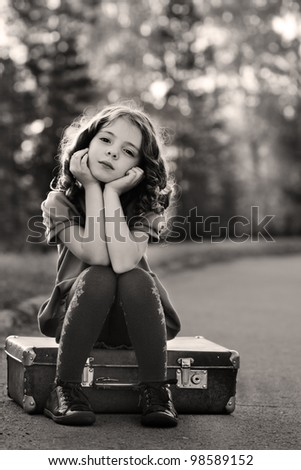 resentful girl on suitcase - stock photo