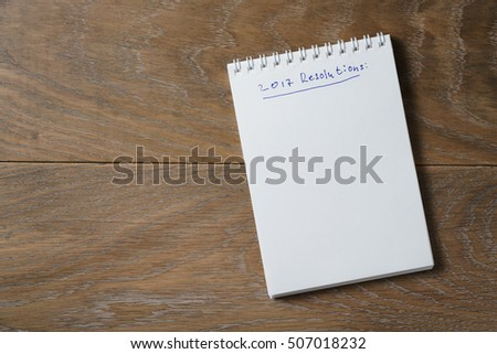 2017 resolutions list on notepad on wood table, blank notepad for your text