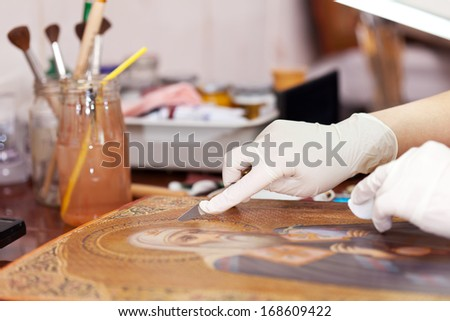 restorer cleaning old icon with spatula at restoration workshop - stock photo