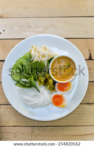 Rice noodles in (with) fish curry sauce / Traditional Thai cuisine, rice vermicelli   served with boiled egg  and vegetable  on wood table.Selective Focus.  - stock photo