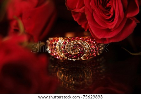 Ring with diamonds & red roses on the bacground shallow DOF