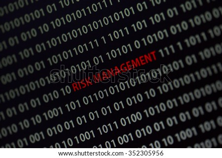 'Risk management' text in the middle of the computer screen surrounded by numbers zero and one. Image is taken in a small angle.