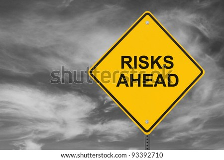 """Risks Ahead"" sign on a stormy sky background - stock photo"