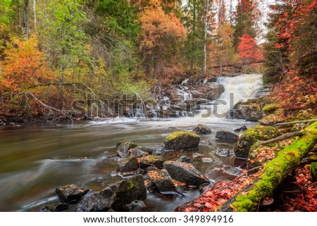 river with waterfall and rocks during autumn - stock photo