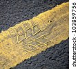 road background with yellow line and tire imprint on the asphalt - stock photo