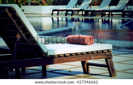 Rolled towel placed on the bed beside the pool on vintage style
