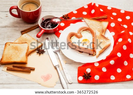 romantic breakfast , heart-shaped fried eggs with sausage with toast, jam , hot black coffee , orange juice and spices on a wooden background