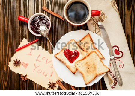 romantic Valentine's Day Breakfast , toast with butter and berry jam , black coffee with cinnamon and spices on a wooden background
