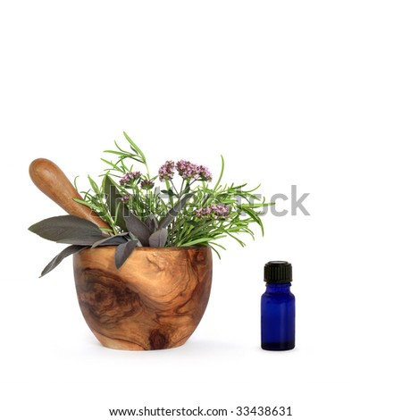 Rosemary, sage and marjoram herb leaves and flowers in an olive wood mortar with pestle and  aromatherapy  essential oil bottle, over white background. - stock photo