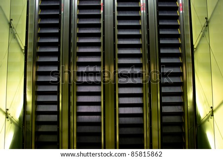 4 rows Escalator with sides lit up inside a shopping mall - stock photo