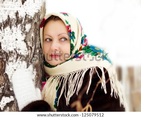 Russian woman in a painted shawl at a birch in winter - stock photo