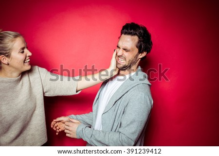 20s Couple in Photostudio in front of beige backdrop having fun fighting in front of the camera with spot light with contrasty vibrant look kissing each other - stock photo