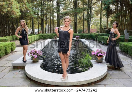 1920's fashion shoot - Three stunning young Caucasian women wearing black vintage appearing dresses with headbands standing around an outdoor pond or pool in garden courtyard - stock photo