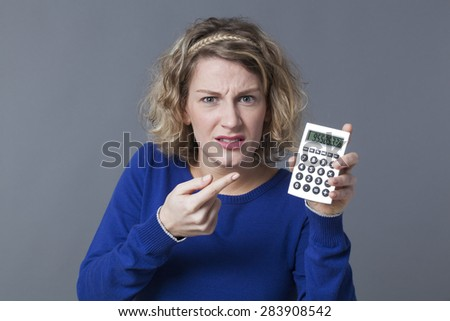 20s girl disappointed by figures shown on her calculator - stock photo