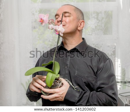 40s man is smelling a pink blooming orchid indoors. Handsome caucasian 40s man smiling portrait on grey background with black shirt holding orchid in pot. - stock photo