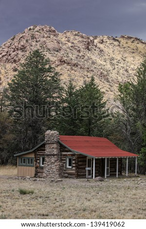 1880's Stafford homestead cabin (later a guest cabin) hunkered in Bonita Canyon of Chiricahua National Monument, Arizona, during Spring thunderstorm/Historic Log and Frame 1880s Cabin/Stafford cabin - stock photo