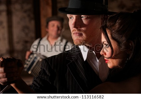 1920s style Tango dancers looking ahead with bandoneon player in background