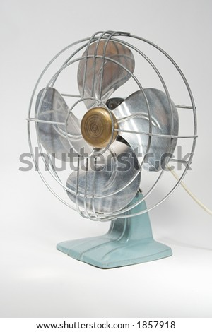 1940s vintage electric fan with metal blades with white background.