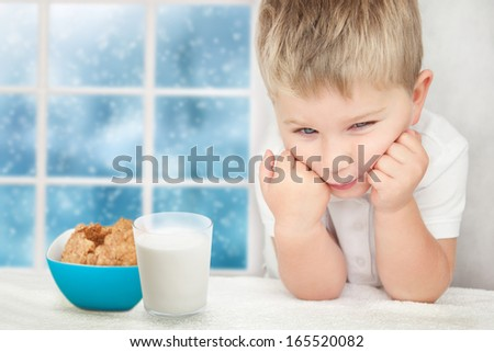 Sad little boy with glass of milk and cookies. Lack of appetite concept. - stock photo