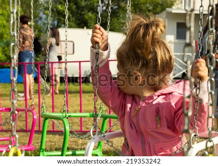 Sad little girl sitting on swing in a park, looks for her mum - stock photo