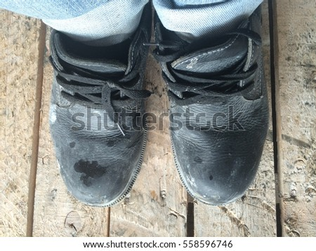 Safety Shoes Black worn on wood.
