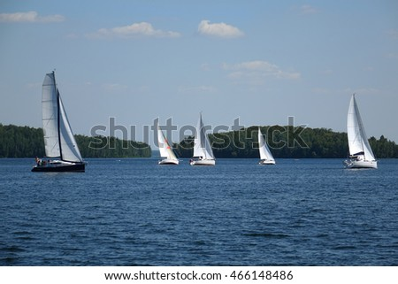 Sailboats floating in the water of the lake.
