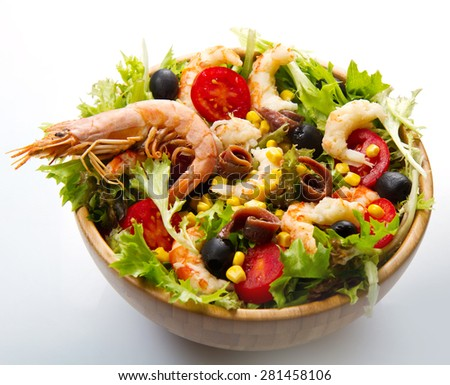 salad of shrimp, mixed greens, black olives anchovies and tomatoes isolated on white - stock photo